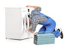 Hersteller die een wasmachine probeert te bevestigen Stock Foto's