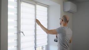 Hersteller die nieuwe gestreepte zonneblinden installeren op een venster in vlakte die boor gebruiken stock video