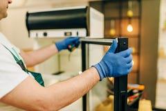 Hersteller in eenvormige reparatiesijskast thuis stock afbeeldingen