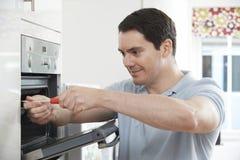 Hersteller Fixing Domestic Oven In Kitchen royalty-vrije stock afbeelding