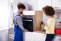 Hersteller Fixing Oven In Kitchen royalty-vrije stock afbeeldingen