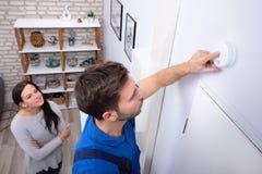 Hersteller Installing Smoke Detector op Muur royalty-vrije stock afbeeldingen