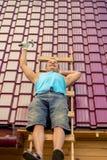 Hersteller op een ladder op het dak terwijl het rusten stock afbeelding