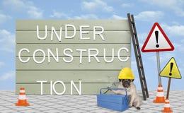 Herstellerpug puppyhond met gele veiligheidshelm, die naast houten raadsteken in aanbouw gaan zitten, met tekst royalty-vrije stock afbeeldingen