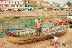 Herstellers die lekke vissersboot op rivierbanken herstellen van Indische stad met historische ghats en huizen Stock Afbeeldingen