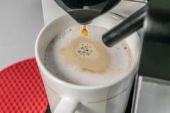 Herstellung Cappuccino - Abschluss herauf die Ansicht des Espressos gie?end aus Kaffeemaschine Cuppuccino hat die Hauptbestandtei lizenzfreie stockfotos