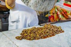 Herstellung das Vorbereiten einer Reihe der heißen karamellisierten Nüsse Stockfotos