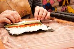 Herstellung der gerollten Sushi in einer Bambussushi-Matte Stockbilder