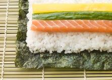 Herstellung der gerollten Sushi in einer Sushi-Matte Stockfoto