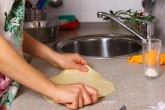 Herstellung der Pizza durch weibliche Hände auf Küchentisch Lizenzfreie Stockfotos