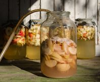 Herstellung des Apfelessigs - Apfel bessert das Schwimmen auf Wasser in einem Glas aus stockbilder