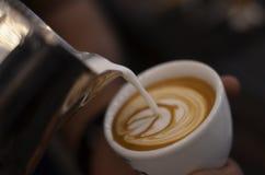 Herstellung des Cappuccinos mit Lattekunst Stockbild