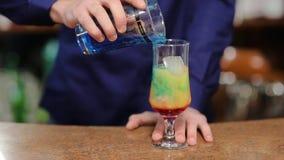 Herstellung des Cocktails, das blaue Flüssigkeit in das Glas füllt stock footage