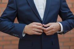 Herstellung des Geschäftsblickes, Nahaufnahme des Mannes seine Jacke knöpfend Lizenzfreie Stockbilder