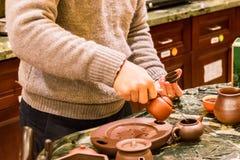 Herstellung des heißen chinesischen Tees mit kleinen keramischen Töpfen Lizenzfreie Stockfotos