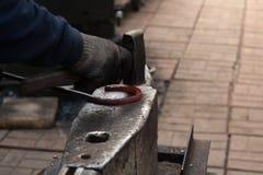 Herstellung des Hufeisens von erhitzter roter Stange Stockbild