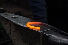 Herstellung des Hufeisens von erhitzter roter Stange Lizenzfreie Stockfotos