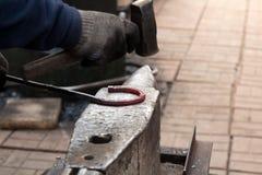 Herstellung des Hufeisens von erhitzter roter Stange Stockfotografie