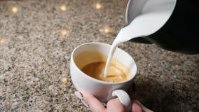 Herstellung des Kaffees Barista Prepares Coffee Vorbereitung von Latte Barista, das heiße Milch in einen Becher Espresso gießt La stock footage