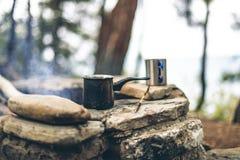 Herstellung des Kaffees im cezve auf dem Kamin beim Kampieren oder Wandern Kaffee auf Lagerfeuer lizenzfreie stockfotos