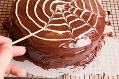 Herstellung des Spinnennetzes auf dem Schokoladenkuchen Stockfoto