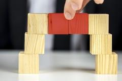 Herstellung einer Brücke mit hölzernen Spielzeugwürfeln lizenzfreies stockfoto