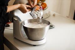 Herstellung einer Creme für selbst gebackene Kuchen auf einem Mischer Lizenzfreie Stockfotos