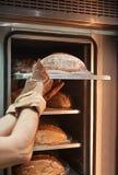 Herstellung eines Brotes Vertikales Foto des Bäckers in den Arbeitshandschuhen, die das heiße Brot aus dem Ofen heraus nehmen stockbild