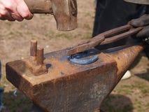 Herstellung eines Hufeisens auf einem Amboss in der Schmiede stockbilder