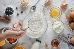 Herstellung Pfannkuchen, Kuchen, Backen von den B?ckerh?nden, die Mehl in der Sch?ssel gie?en oder sieben Konzept des Kochens von stockfotos