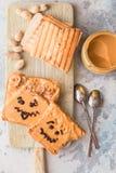 Herstellung von Erdnussbuttersandwichen mit Persönlichkeit! Spaßsmileygesicht an gezeichnet mit Stau Sahnige Erdnussbutter mit St stockbilder
