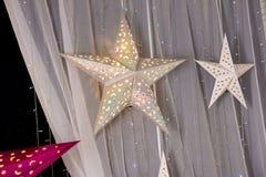 Herstellung von glänzenden dekorativen Sternen von verschiedenen Farben stockfotos