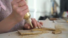 Herstellung von hölzernen Dekorationen von hölzerner Nr. fünf und vom goldenen Funkeln arbeitsplatz stock video