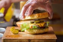Herstellung von köstlichem selbst gemachtem Maxi Burger mit gegrilltem Rindfleischsteak, Kopfsalat, Käse, Tomate, Zwiebel, Barbec stockfotos