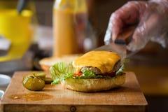 Herstellung von köstlichem selbst gemachtem Maxi Burger mit gegrilltem Rindfleischsteak, Kopfsalat, Käse, Tomate, Zwiebel, Barbec lizenzfreies stockfoto
