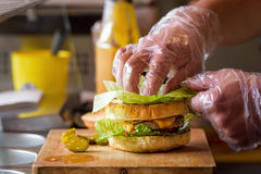 Herstellung von köstlichem selbst gemachtem Maxi Burger mit gegrilltem Rindfleischsteak, Kopfsalat, Käse, Tomate, Zwiebel, Barbec lizenzfreies stockbild