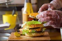 Herstellung von köstlichem selbst gemachtem Maxi Burger mit gegrilltem Rindfleischsteak, Kopfsalat, Käse, Tomate, Zwiebel, Barbec lizenzfreie stockbilder