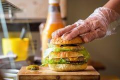 Herstellung von köstlichem selbst gemachtem Maxi Burger mit gegrilltem Rindfleischsteak, Kopfsalat, Käse, Tomate, Zwiebel, Barbec lizenzfreie stockfotografie