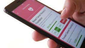Herstellung von Nächstenliebe-Spende zur Krebs-Nächstenliebe unter Verwendung Smartphone-APP stock footage