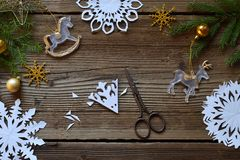 Herstellung von Papierschneeflocken mit Ihren eigenen Händen Children& x27; s DIY Konzept der frohen Weihnachten und des neuen Ja lizenzfreie stockfotografie