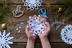 Herstellung von Papierschneeflocken mit Ihren eigenen Händen Children& x27; s DIY Konzept der frohen Weihnachten und des neuen Ja stockbild