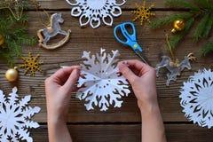 Herstellung von Papierschneeflocken mit Ihren eigenen Händen Children& x27; s DIY Konzept der frohen Weihnachten und des neuen Ja stockbilder