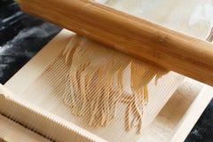 Herstellung von Spaghettis alla chitarra mit einem Werkzeug Lizenzfreie Stockbilder