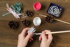 Herstellung von Weihnachtsdekorationen von den Kiefernkegeln Schritt 2 Stockbild