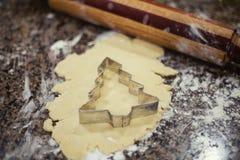 Herstellung von Weihnachtsplätzchen mit Zuckerplätzchenteig und Plätzchenschneidern lizenzfreie stockfotografie