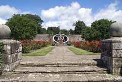 Herstmonceux Castle rose garden entrance, sundial, and John Flamsteed statue Royalty Free Stock Image