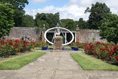 Herstmonceux Castle rose garden with a sundial and John Flamsteed statue Stock Image