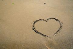 Hert in zand door golven wordt gewassen die Royalty-vrije Stock Afbeelding