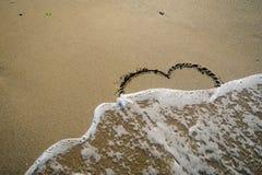 Hert in zand door golven wordt gewassen die Royalty-vrije Stock Foto