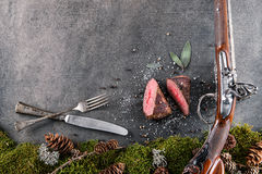 Herten of hertevleeslapje vlees met antieke lange kanon, bestek en ingrediënten zoals overzees zout, kruiden en peper, voedselach Royalty-vrije Stock Fotografie
